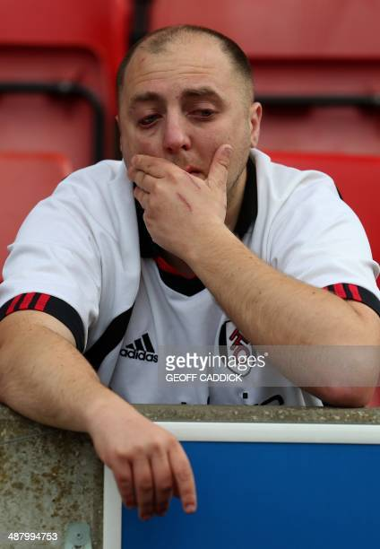 A Fulham fan reacts in the stands following his team`s relegation after losing 41 during the English Premier League football match between Stoke City...