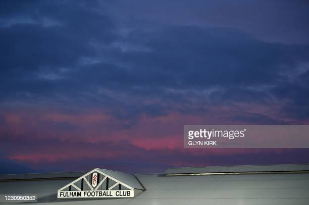 Fulham Football Club logo is pictured on the roof of a stand as the sun sets beyond, ahead of the English Premier League football match between...