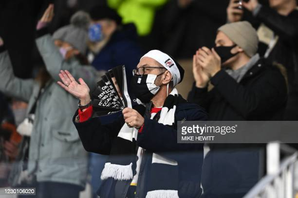 Fulham supporters wearing protective face coverings to combat the spread of the coronavirus, cheer from their socially-distanced seats ahead of the...
