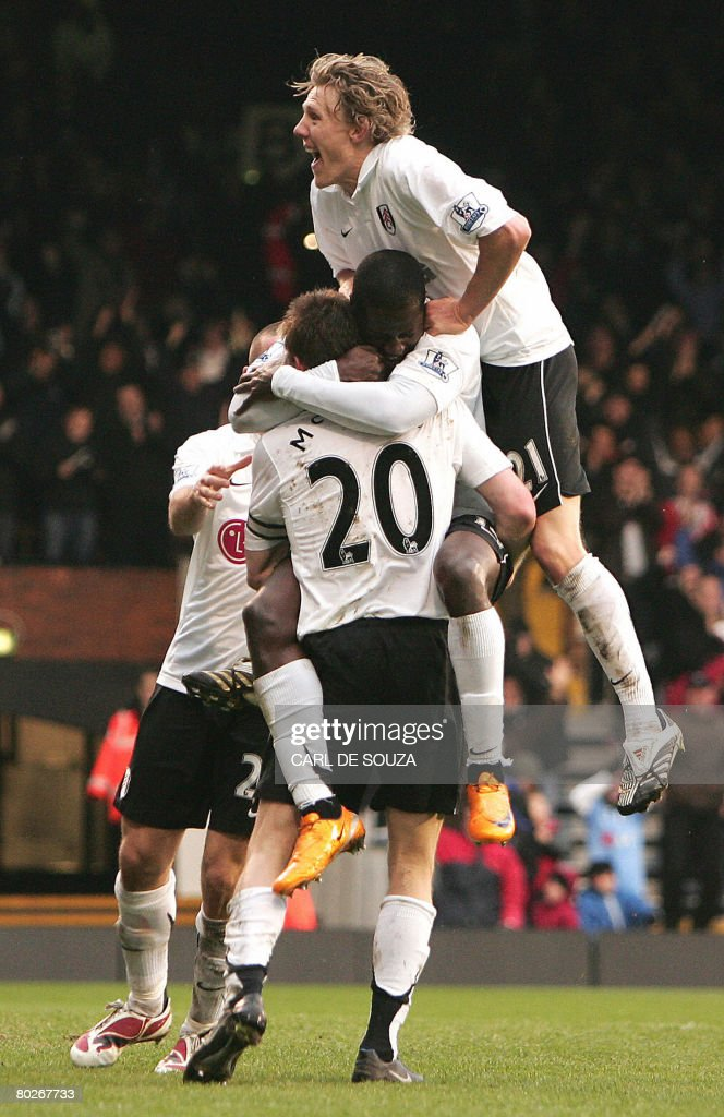 Fulham's Eddie Johnson (Orange boots), captain Brian McBride (C, standing) and Jimmy Bullard (R, Up) celebrate McBride's goal during their Premiership match against Everton at Fulham's Craven Cottage Stadium on March 16, 2008. AFP PHOTO/CARL DE SOUZA --- Mobile and website use of domestic English football pictures are subject to obtaining a Photographic End User Licence from Football DataCo Ltd Tel : +44 (0) 207 864 9121 or e-mail accreditations@football-dataco.com - applies to Premier and Football League
