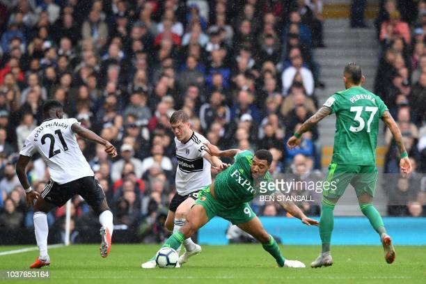 Fulham's English defender Alfie Mawson vies with Watford's English striker Troy Deeney during the English Premier League football match between...