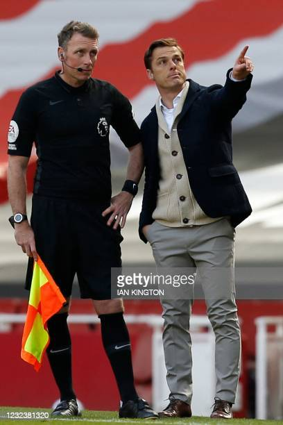 Fulham's English manager Scott Parker gestures as he speaks to an assistant referee during the English Premier League football match between Arsenal...