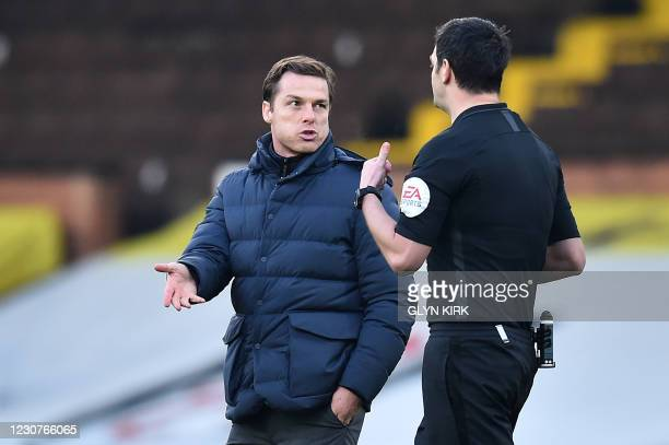 Fulham's English manager Scott Parker speaks with Referee Andy Madley as they walk back onto the pitch for the second half during the English FA Cup...
