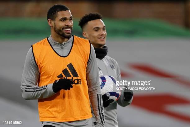 Fulham's English midfielder Ruben Loftus-Cheek and Fulham's English-born US defender Antonee Robinson warm up ahead of the English Premier League...