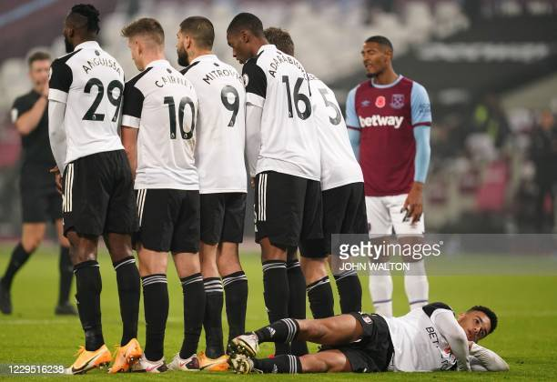 Fulham's Englishborn US defender Antonee Robinson lies down behind a defensive wall ahead of West Ham taking a free kick close to goal during the...