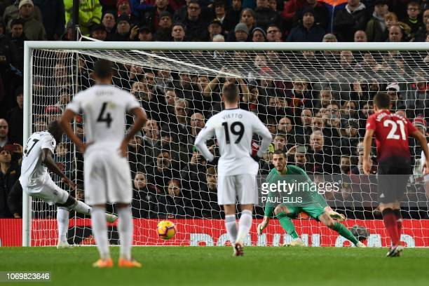 Fulham's French striker Aboubakar Kamara shoots and scores from the penalty spot during the English Premier League football match between Manchester...
