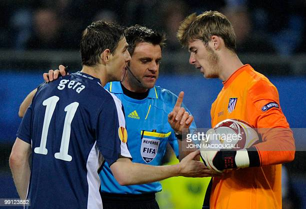 Fulham's Hungarian midfielder Zoltan Gera argues with Atletico Madrid's goalkeeper David de Gea next to Italian Referee Nicola Rizzoli during the...