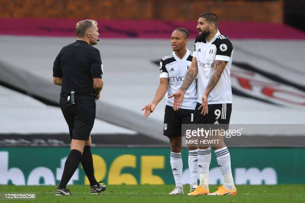 Fulham's Jamaican striker Bobby Decordova-Reid and Fulham's Serbian striker Aleksandar Mitrovic argue with Referee Graham Scott after he shows...
