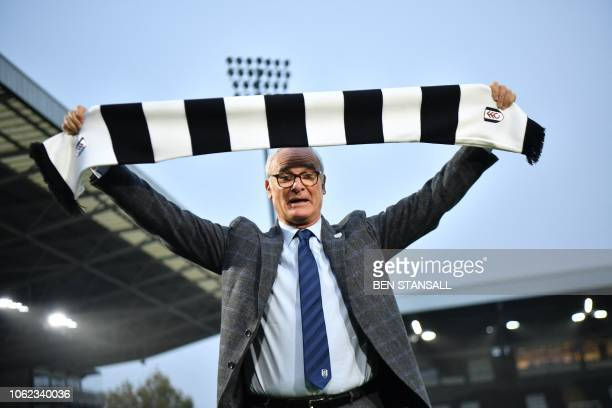 Fulham's new Italian manager Claudio Ranieri poses with a team scarf on the pitch at the club's Craven Cottage stadium on November 16 2018 /...