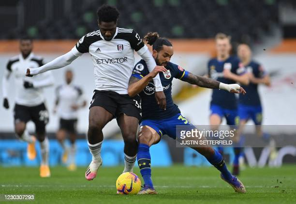 Fulham's Nigerian defender Ola Aina fights for the ball with Southampton's English midfielder Theo Walcott during the English Premier League football...