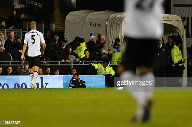 Fulham's Norwegian defender Brede Hangeland leaves the pitch after being given a straight red card from referee Lee Probert following a tackle on...