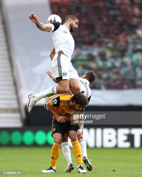 Fulham's Serbian striker Aleksandar Mitrovic jumps above Wolverhampton Wanderers' Portuguese midfielder Ruben Neves during the English Premier League...