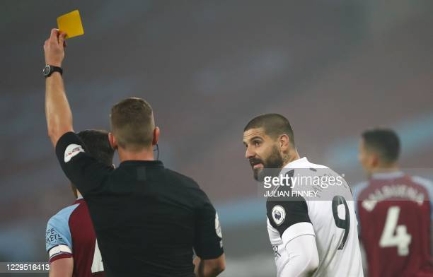 Fulham's Serbian striker Aleksandar Mitrovic looks back at the Referee Robert Jones as he gets shown a yellow card during the English Premier League...
