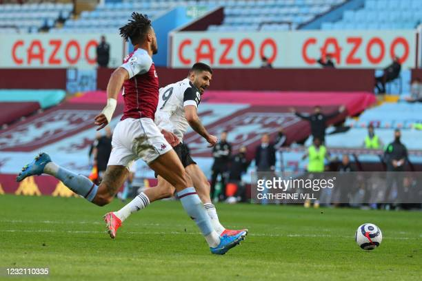 Fulham's Serbian striker Aleksandar Mitrovic shoots to score the opening goal after a mistake from Aston Villa's English defender Tyrone Mings during...