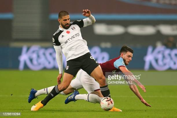 Fulham's Serbian striker Aleksandar Mitrovic vies for the ball against West Ham United's English midfielder Declan Rice during the English Premier...