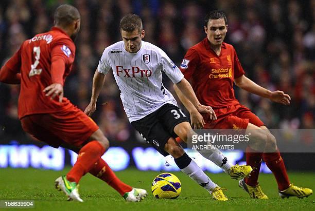 Fulham's Swedish midfielder Alexander Kacaniklic vies with Liverpool's English defender Glen Johnson and English midfielder Stewart Downing during...