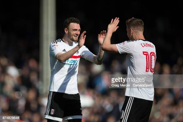 Fulham's Tom Cairney celebrates with team mate Scott Malone at full time of the Sky Bet Championship match between Fulham and Brentford at Craven...