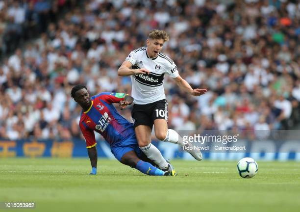 Fulham's Tom Cairney is challenged by Crystal Palace's Jeffrey Schlupp during the Premier League match between Fulham FC and Crystal Palace at Craven...