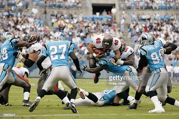 Full Back Mike Alstott of the Tampa Bay Buccaneers dives over Defensive Tackle Brentson Buckner of the Carolina Panthers during the NFL game at...