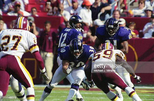 Full back Obafemi Ayanbadejo of the Baltimore Ravens blocks Linebacker Shawn Barber of the Washingtin Redskins so that his teammate and ball carrier...