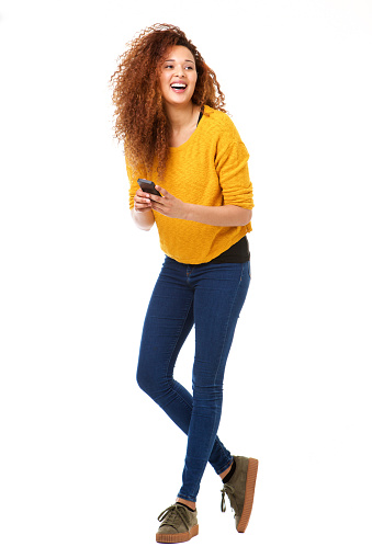 Full body happy woman with cellphone laughing against isolated white background 1035693082