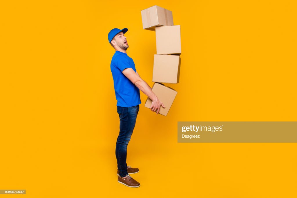 Full body length size, side profile view of handsome scared, shocked bearded deliver in uniform holding four large big flying up in air boxes in arms, isolated over bright vivid yellow background : Stock Photo