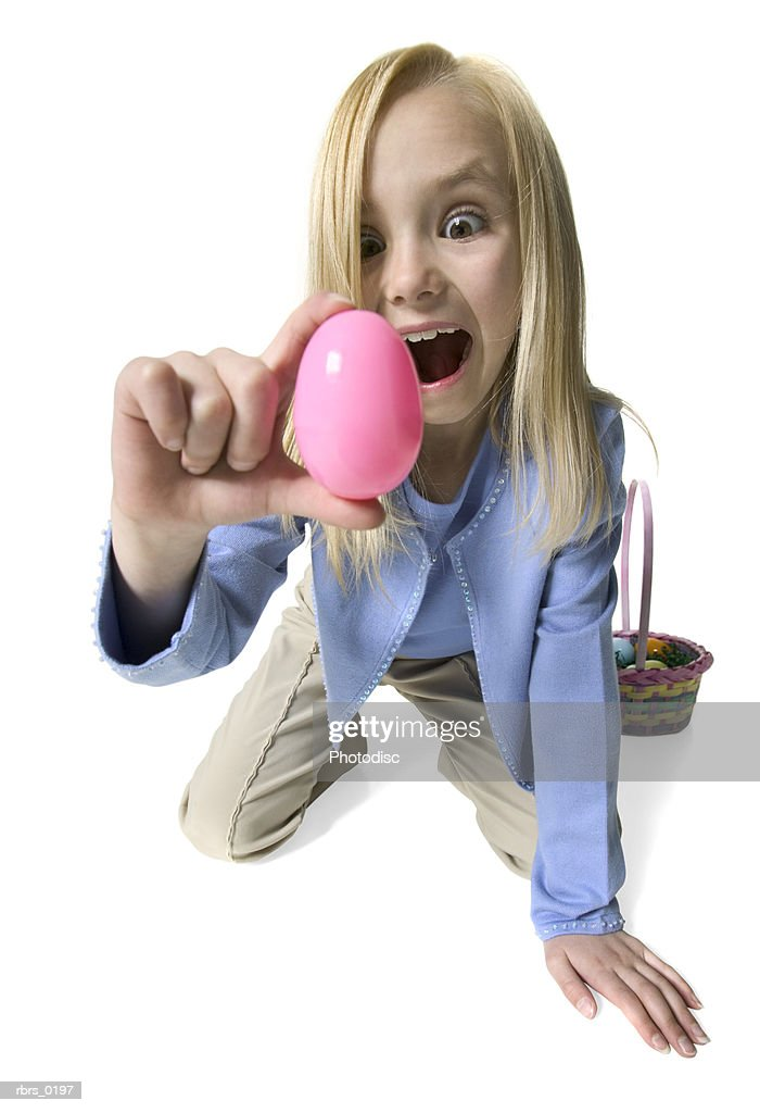 full body portrait of a female child as she acts excited after finding a pink easter egg : Foto de stock