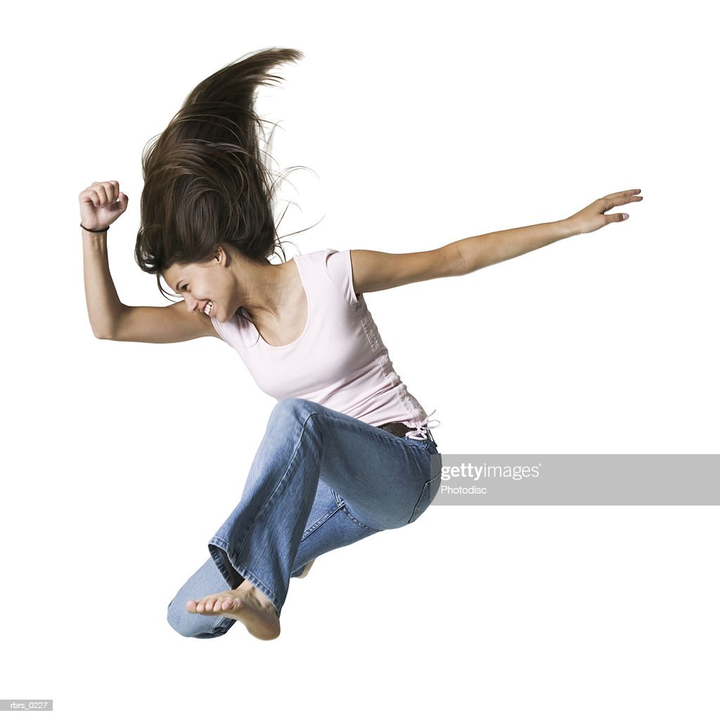 full body portrait of a teenage female in jeans and a pink shirt as she jumps through the air : Foto de stock