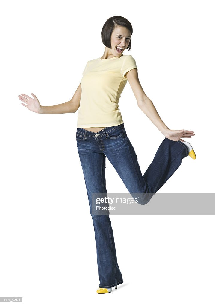 full body portrait of a teenage female in jeans and a yellow shirt she kicks up her foot and smiles : Foto de stock