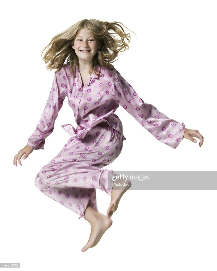 full body portrait of a teenage female in pink pajamas as she jumps up in the air : Foto de stock