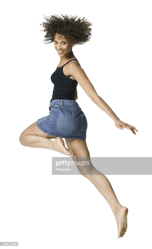 full body portrait of a young adult female in a black tank top as she playfully skips along : Foto de stock