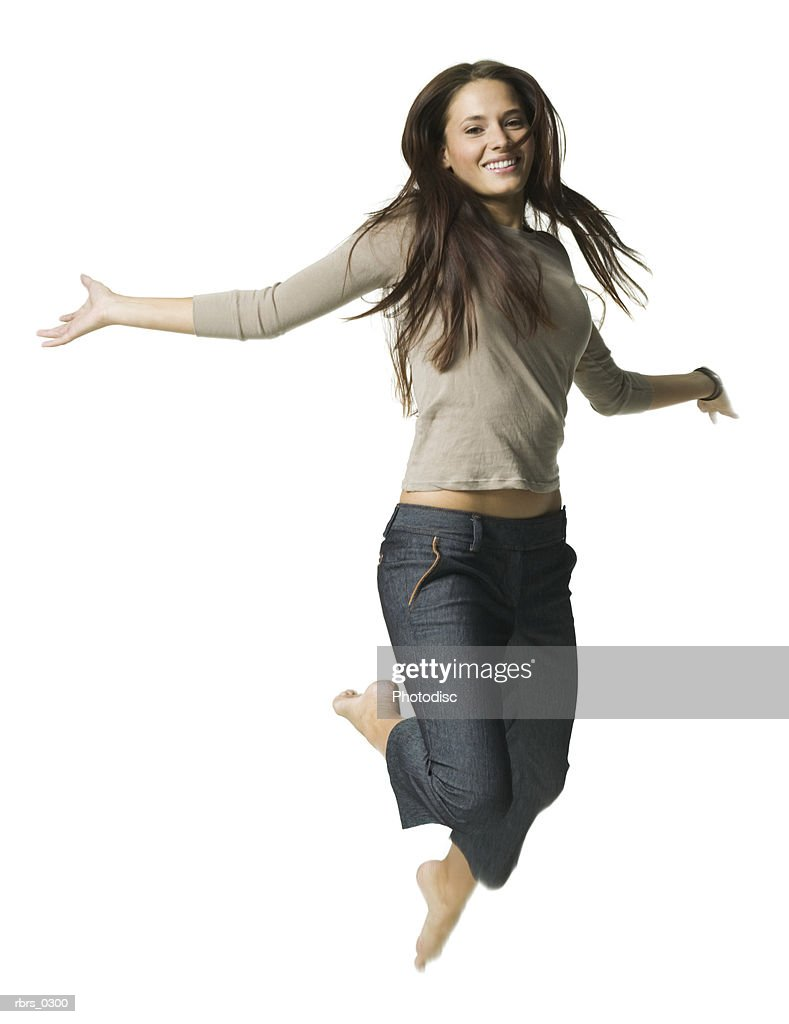 full body portrait of a young adult female in a brown sweater as she jumps through the air : Foto de stock