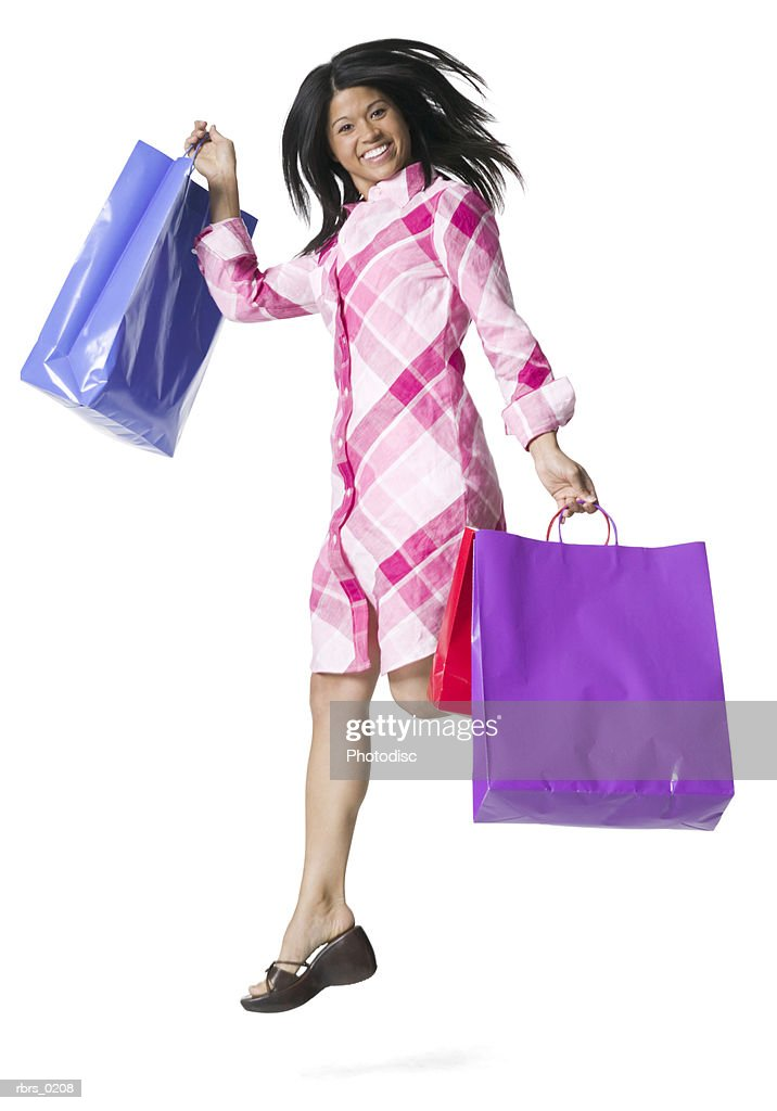 full body portrait of a young adult female in a pink patterned dress as she jumps with shopping bags : Foto de stock