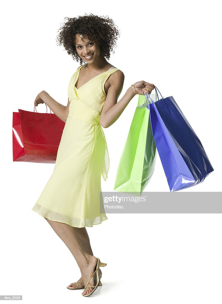 full body portrait of a young adult female in a yellow dress as she poses with shopping bags : Foto de stock
