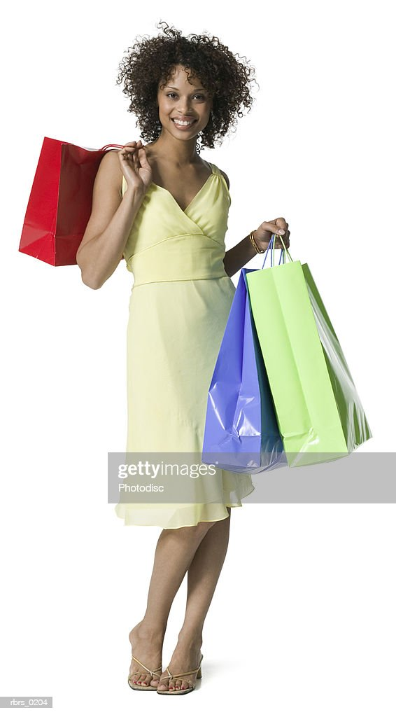 full body portrait of a young adult female in a yellow dress as she stands with shopping bags : Foto de stock