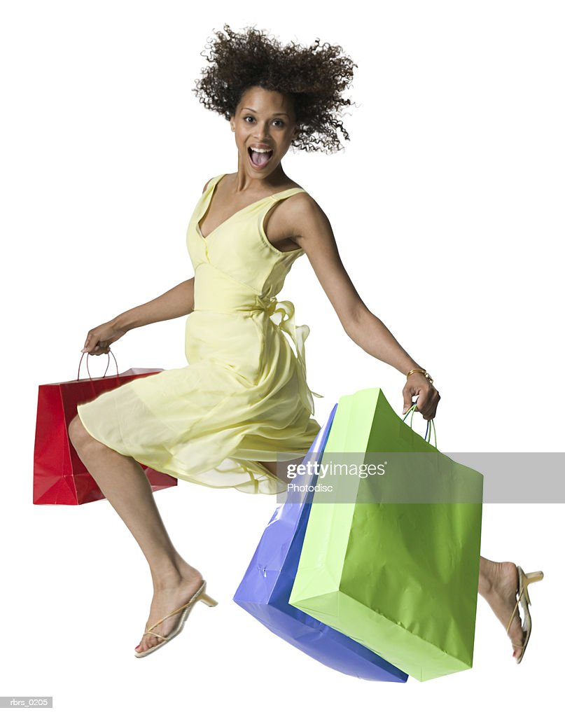 full body portrait of a young adult female in a yellow dress as she jumps up with shopping bags : Foto de stock