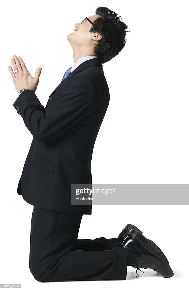 full body portrait of a young adult male in a suit as he gets down on his knees and begs : Foto de stock