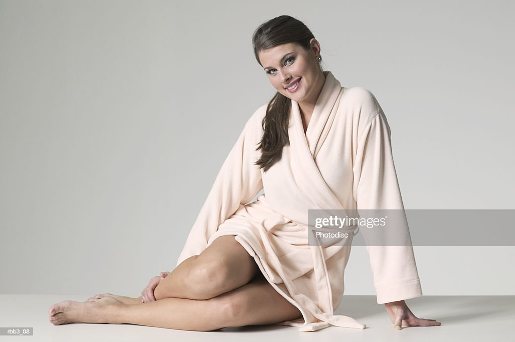 full body portrait of a young brunette woman in a bathrobe : Stockfoto