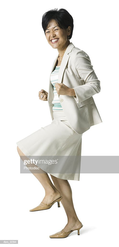 full body portrait of an adult business woman in a tan outfit as she strikes a celebratory pose : Stockfoto