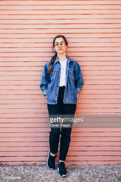 full body portrait of an attractive young woman on a pink brick wall. vertical image - full body isolated photos et images de collection