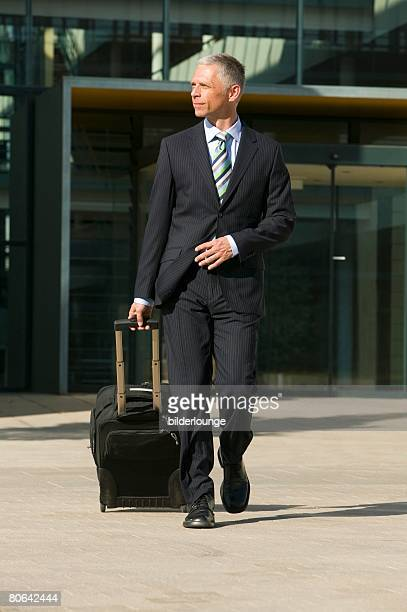 full body portrait of mature businessman with carry-on suitcase