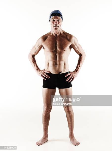 full body portrait of mature male swimmer - zwembroek stockfoto's en -beelden
