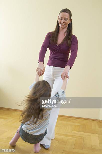 full body portrait of mother dancing with her little daughter