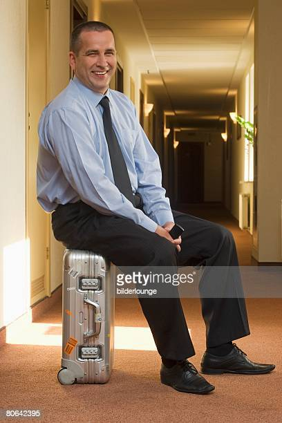 full body portrait of smiling mature businessman sitting on suitcase in hotel corridor
