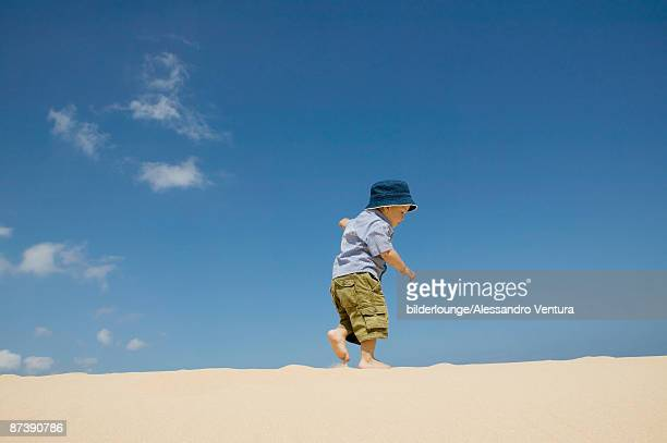 full body portrait of toddler walking on beach
