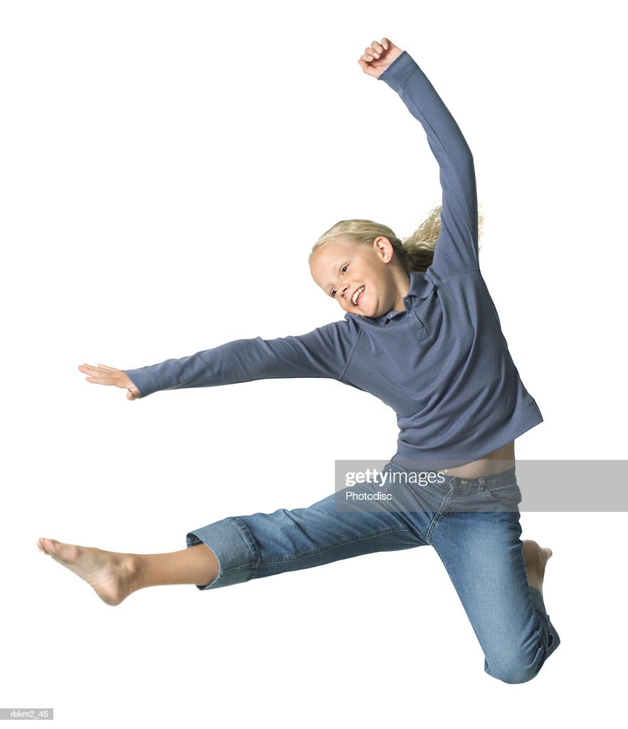 full body shot of a blonde female child as she jumps and kicks through the air : Stockfoto