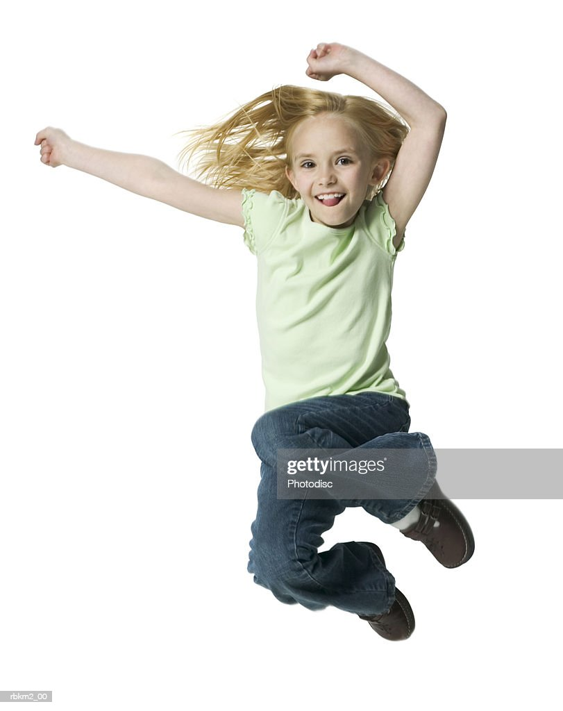full body shot of a blonde female child as she jumps through the air : Stockfoto