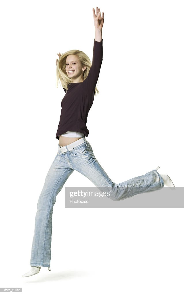 full body shot of a blonde teenage female in a purple shirt as she runs and jumps through the air : Stockfoto