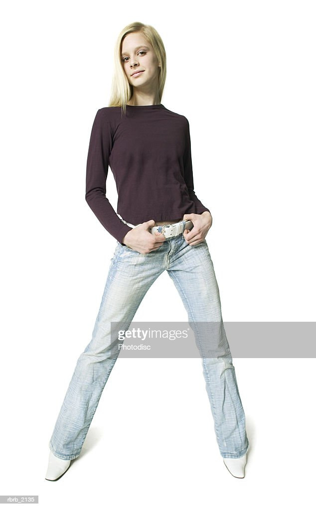 full body shot of a blonde teenage female in a purple shirt as she smiles at the camera : Stockfoto