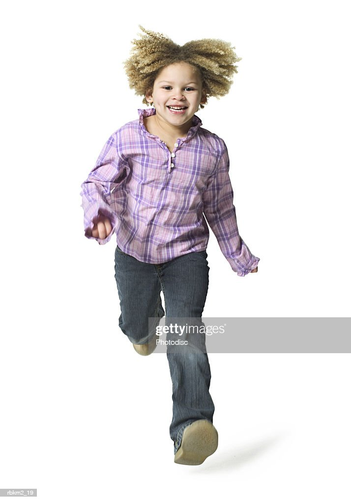 full body shot of a curly haired female child as she runs forward and jumps : Stockfoto